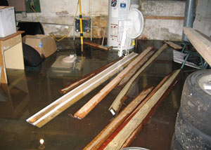 A severely flooding basement in Cortland, with lumber and personal items floating in a foot of water