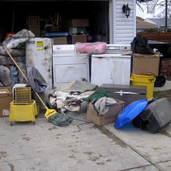 Soaked, wet personal items sitting in a driveway, including a washer and dryer in Fairport.